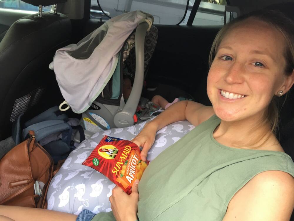 Woman sitting in a car with a snack bag, Sun-Maid dried fruit pack in hand