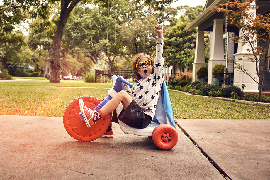 Child in cape happily riding a tricycle